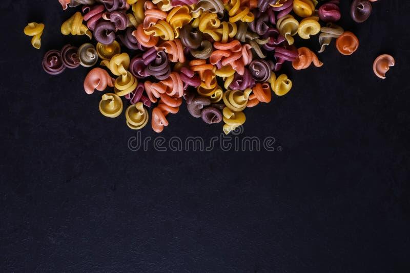 Stubarwny makaron z dodatkiem naturalnego jarzynowego barwidła Rozpraszający na czarnym betonu stole Odgórny widok, kopii przestr obrazy stock