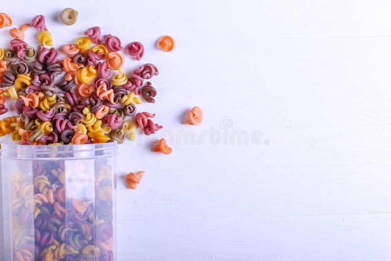 Stubarwny makaron z dodatkiem naturalnego jarzynowego barwidła Rozpraszający od puszki na białym stole Odgórny widok, kopii przes fotografia stock