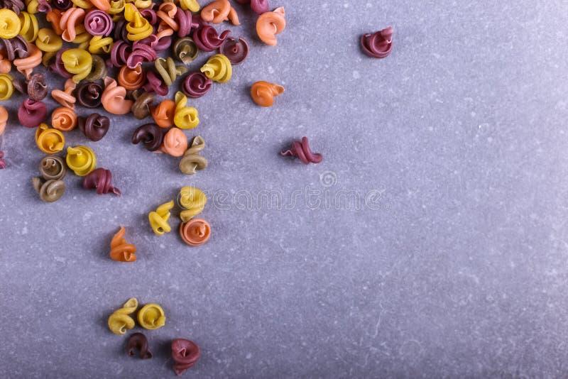 Stubarwny makaron z dodatkiem naturalnego jarzynowego barwidła Rozpraszający na betonowym stole Odgórny widok, kopii przestrzeń zdjęcie stock
