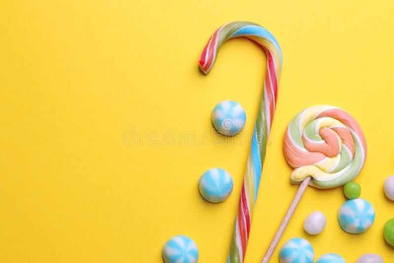 Stubarwny round cukierek i barwioni lizaki na żółtym jaskrawym tle zdjęcia royalty free