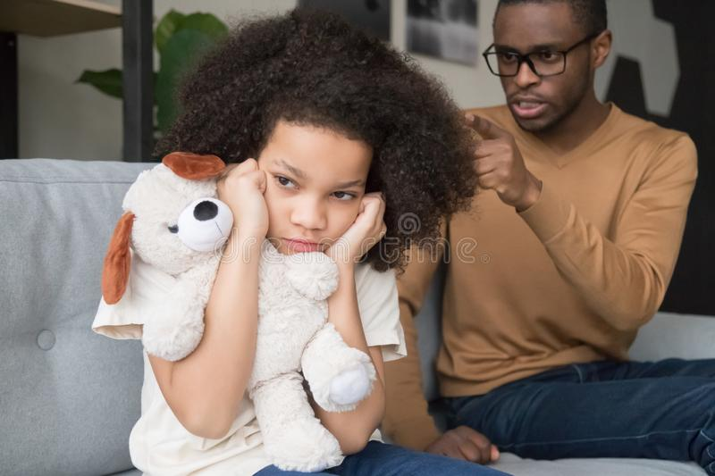 Stubborn african child girl closing ears ignoring angry black dad. Stubborn naughty african preschool child girl closing ears ignoring angry strict black dad royalty free stock photography