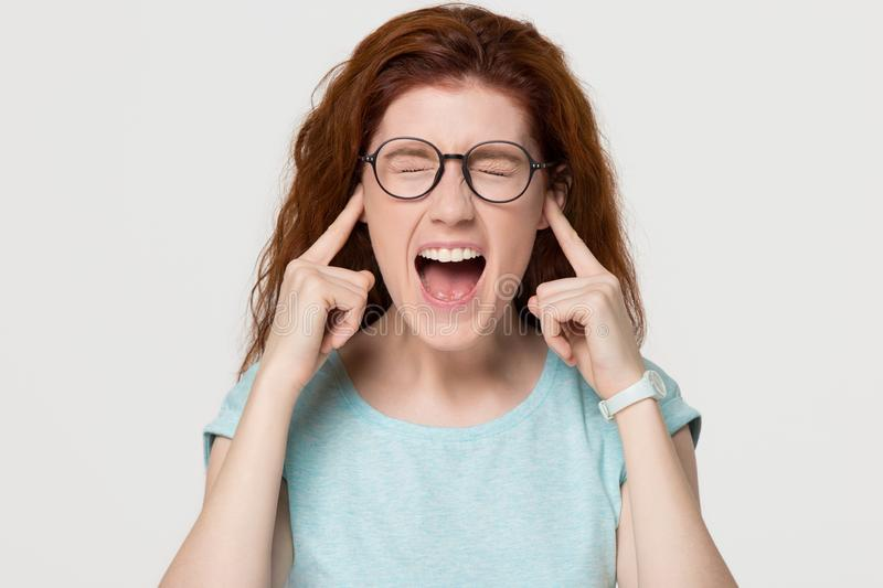 Stubborn angry redhead girl sticking plug fingers in ears screaming. Stubborn angry redhead girl sticking plug finger in ear screaming annoyed not listening stock images