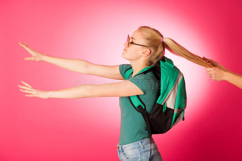 Stubborn, angry schoolgirl resisting to go to school. Wearing backpack and big eyeglasses, someone pulling her for two hair tails royalty free stock photos