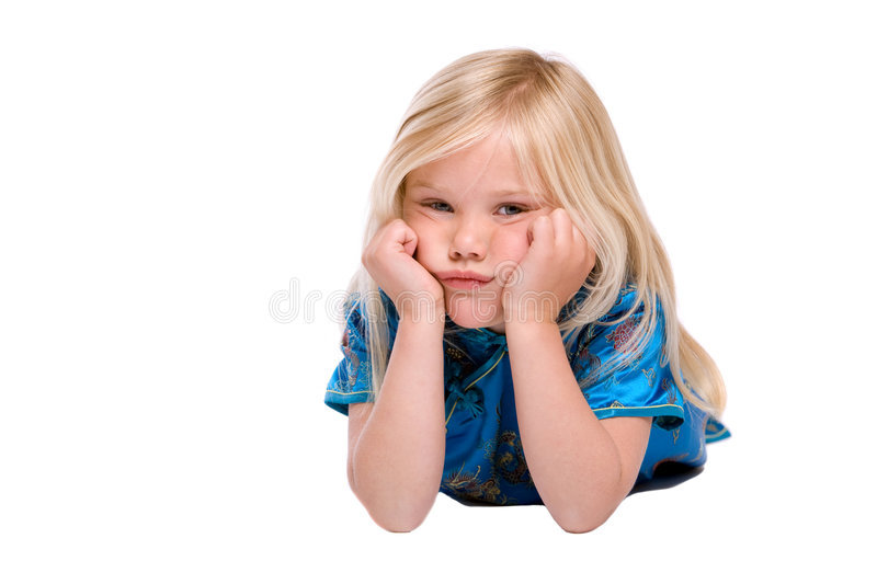 Stubborn and bored. Cute four year old girl lying on the floor looking stubborn royalty free stock photography
