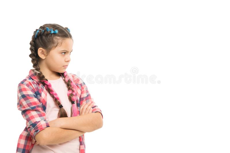 Stubborn child. Disagreement and stubbornness. Girl serious face offended. Kid looks strictly. Girl folded arms on chest. Looks serious copy space white stock photography
