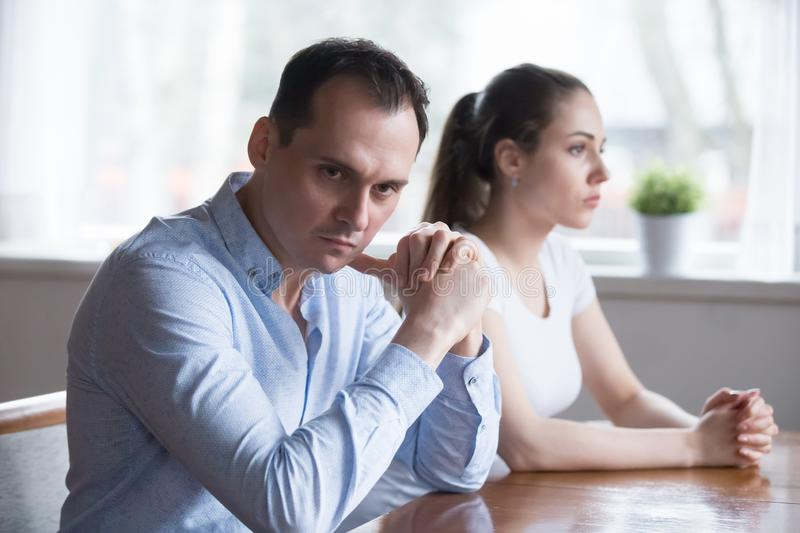 Stubborn couple avoid talking to each other after fight. Stubborn couple avoid looking at each other after serious family fight, men and women not talking sit royalty free stock photos