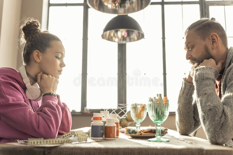 Stubborn daughter drinking pills for slimming and losing weight. Losing weight. Stubborn teenage daughter drinking pills for slimming and losing weight stock images