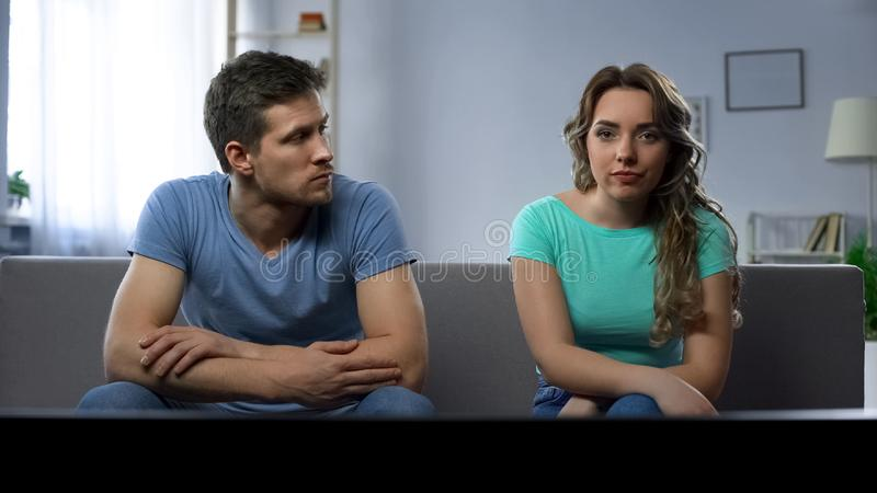 Stubborn girlfriend ignoring her guy silently watching tv, relationship crisis. Stock photo royalty free stock photography