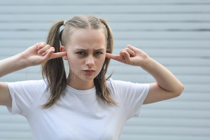 Stubborn, headstrong teen age girl, with fingers in her ear, she does not want to listen. Education problems. Stubborn, headstrong teen age girl, with fingers in royalty free stock photography