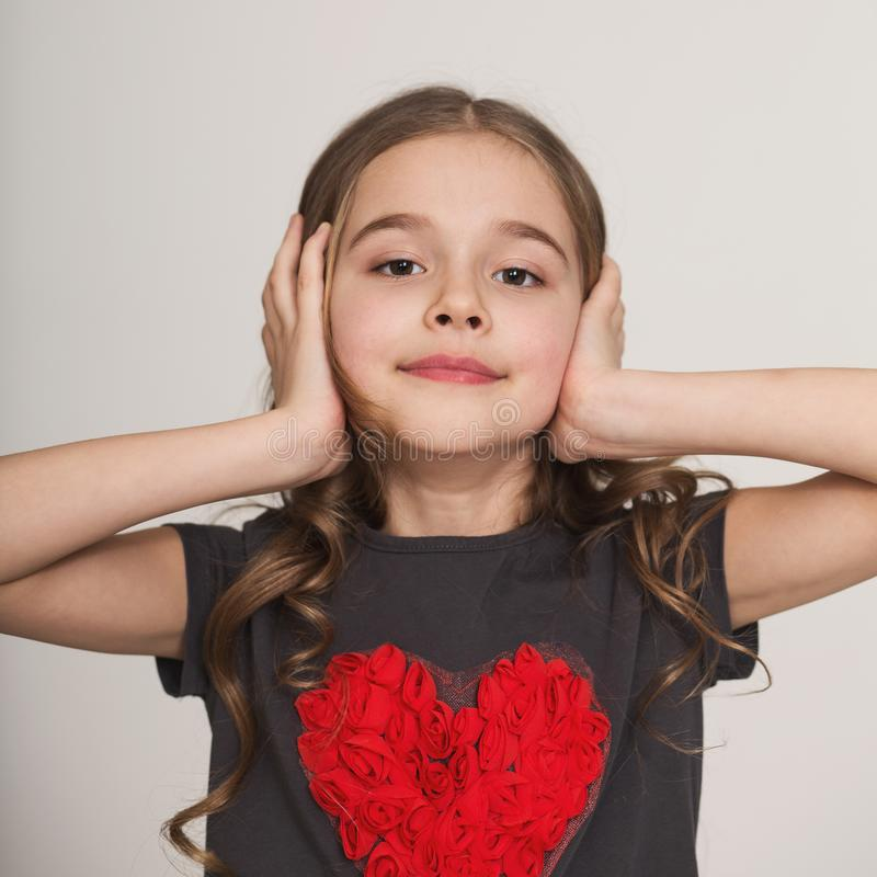 Stubborn little girl blocking her ears with hands stock photo