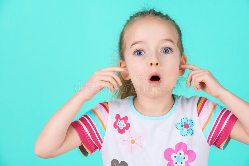 Stubborn little kid with an attitude ignoring parents, blocking her ears with hands. stock photography