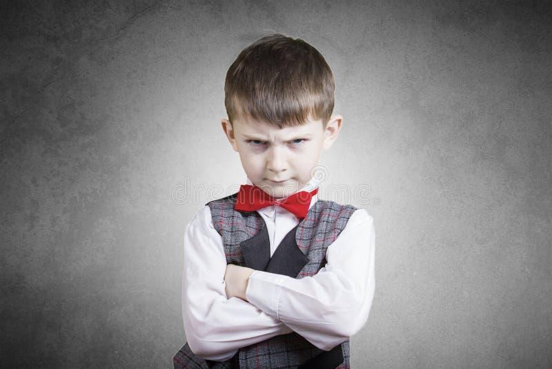 Stubborn,sad,upset little boy. Child over grey background.Facial expression royalty free stock photos