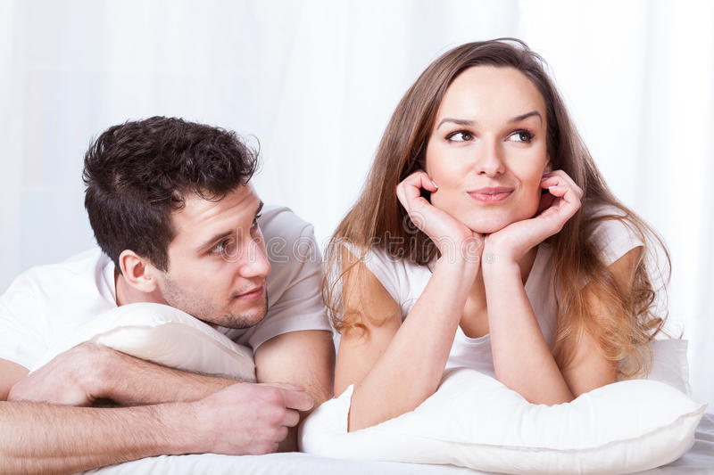 Stubborn woman and loving man. A stubborn confident women and a loving shy men lying in bed stock photo