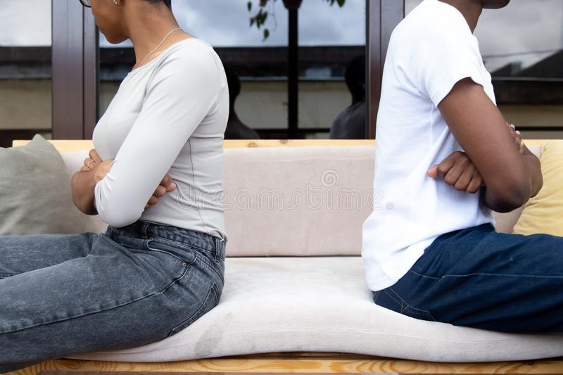 Stubborn young couple avoid talking after fight. Crop close up of offended men and women sit back to back not talking after fight or family conflict, stubborn royalty free stock image