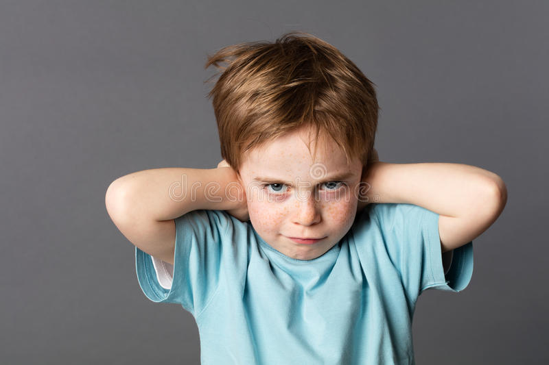 Stubborn young kid teasing, covering closed ears, ignoring parents stock images