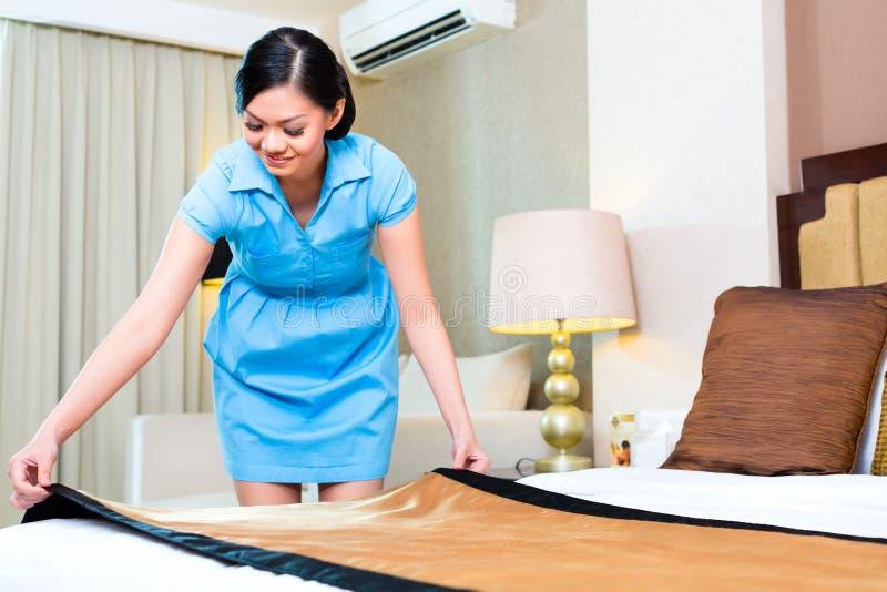 Stubenmädchen, das Bett im asiatischen Hotel macht lizenzfreie stockfotografie