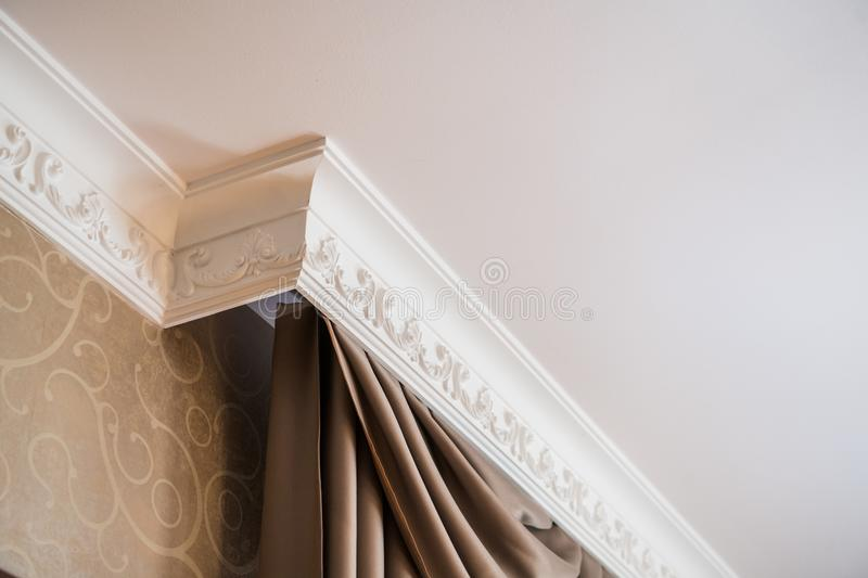 Stucco on the ceiling and curtains in rich apartment royalty free stock image
