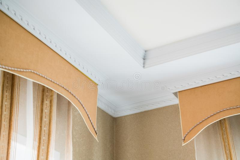 Stucco on the ceiling and curtains in rich apartment royalty free stock photography