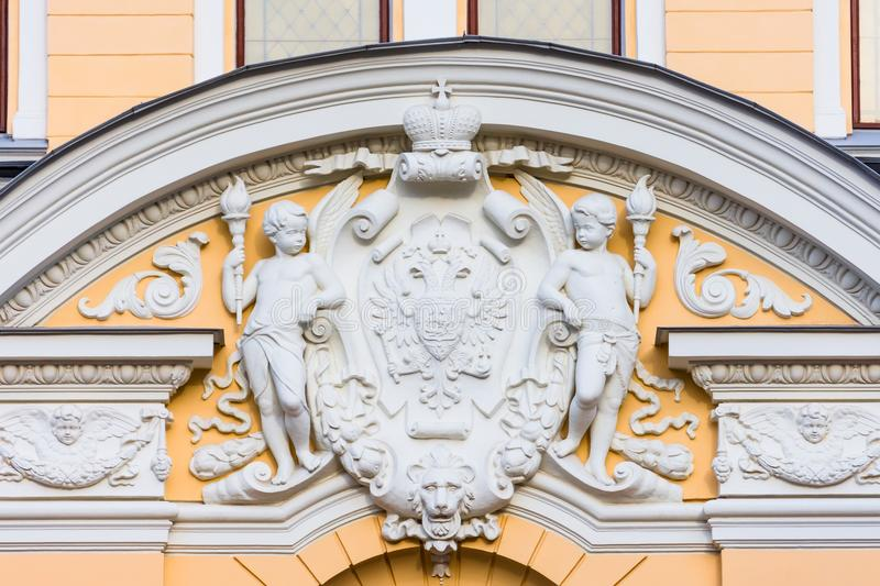 Stucco decoration over the arch - the coat of arms of the two-headed eagle of the Russian Empire with a crown, on the sides are tw stock image