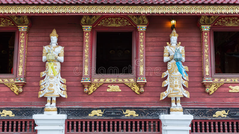 Stucco statue of guardian angel. In salute posture at Wat Mung Muang, Chiangrai, Thailand royalty free stock images
