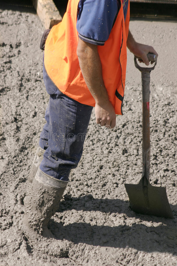 Stuck in cement. This construction worker stands in wet cement with knee high boots covered in cement. He is leaning on his his shovel royalty free stock image
