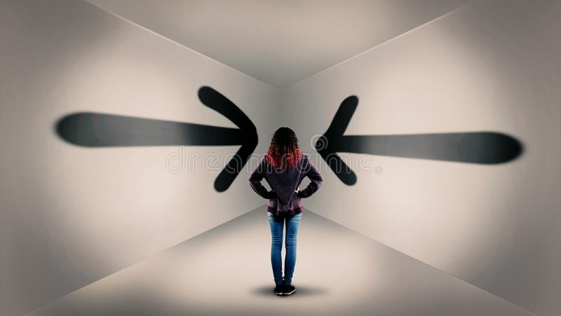 Stuck in the room. Young woman in a room with arrows painted on walls leading to the corner of the room. The concept of stuck in wrong direction royalty free stock photos