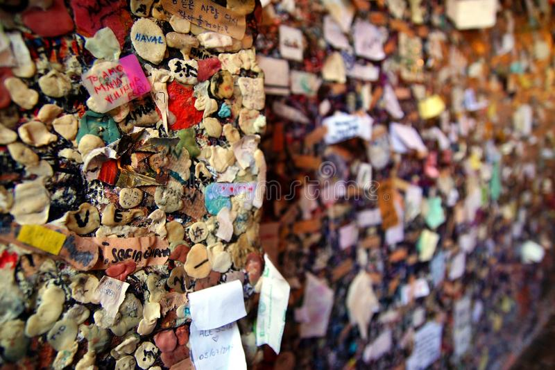 A brick wall covered in used chewing gum with lovers autographs. Casa di Giulietta stock photography