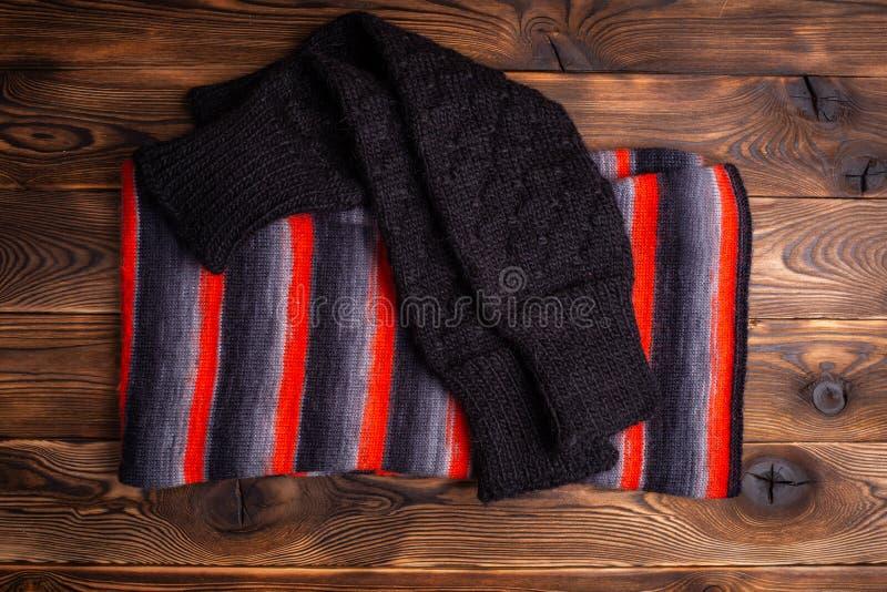 Stucken halsduk i svarta och röda band och svarta stack oversleeves på träbakgrund royaltyfri foto