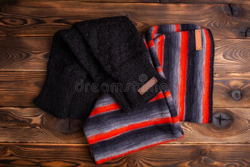 Stucken halsduk i svarta och r?da band och svarta stack oversleeves p? tr?bakgrund royaltyfria bilder
