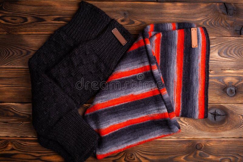 Stucken halsduk i svarta och r?da band och svarta stack oversleeves p? tr?bakgrund royaltyfria foton