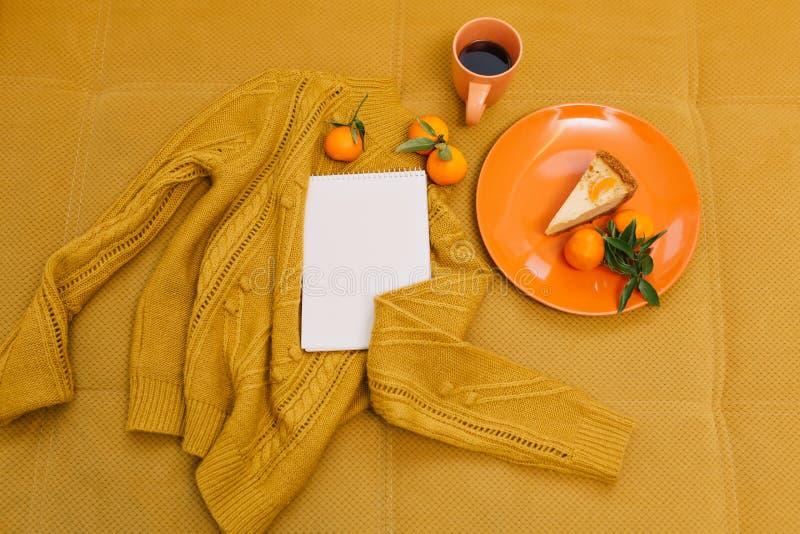 Stucken tröja, kopp kaffe, ostkaka, mandarines, anteckningsbok på orange bakgrund från över arkivbilder