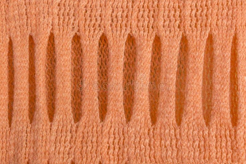 Stucken woolen textur med den härliga holey traceryen av den delikata apelsinen för abstrakta modellbakgrunder royaltyfri fotografi