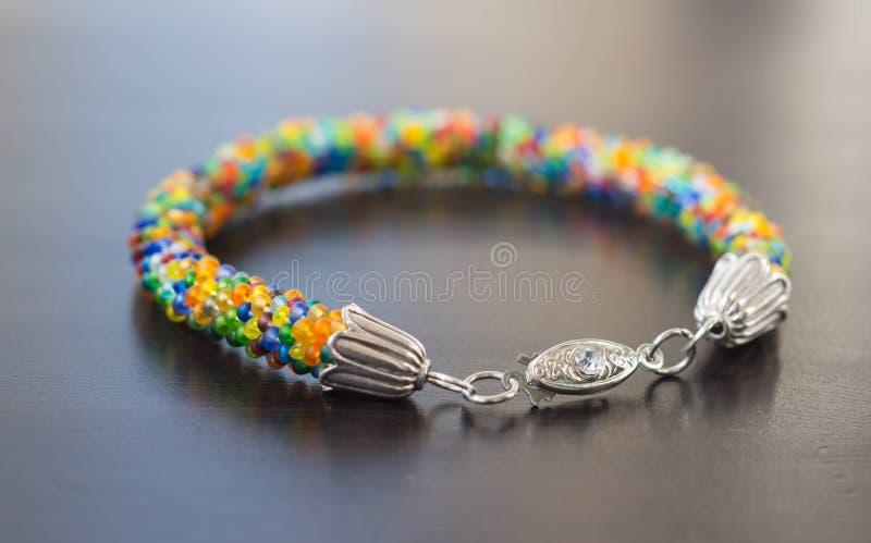 Stuckit armband från små mång--färgade pärlor royaltyfria foton