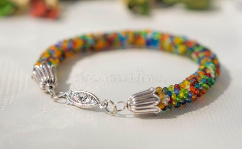 Stuckit armband från små mång--färgade pärlor royaltyfri bild
