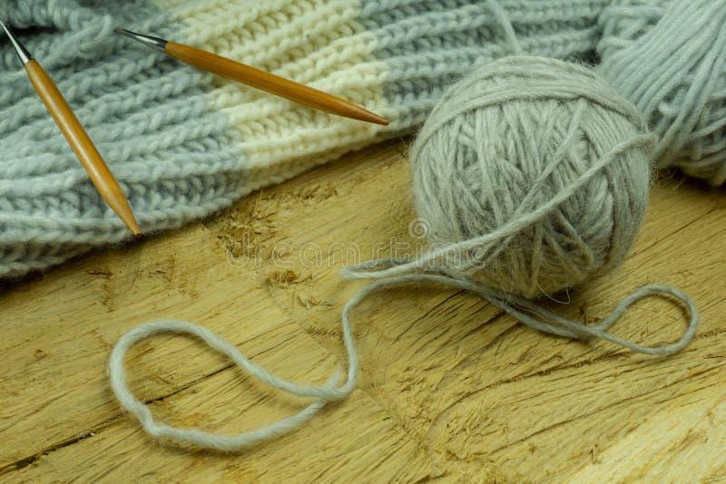 Stuckit från ett grått garn och en tråd för att sticka närbild Sticka som en hobby arkivbild