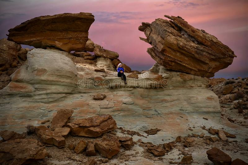 Woman tourist watching sunset sitting on cliff.  Giant toadstool rocks near Lake Powell in Arizona at sunset. Stud Horse Point hiking trail.  Winter travel to stock image