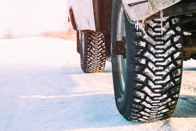 Studded winter car tires. On snow-covered road stock image