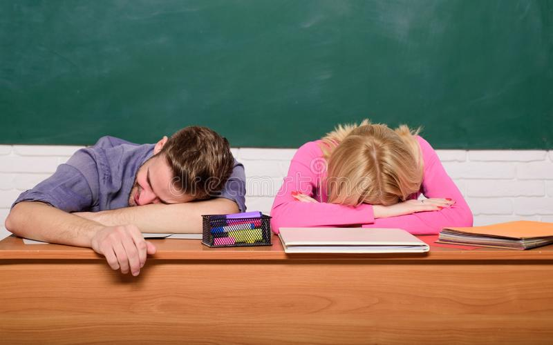 Studenccy żyć zagadnienia Faceta i dziewczyny ucznia chudy na biurku w sali lekcyjnej męczący lub gnuśny Czuć zanudzam Studiować  zdjęcie stock