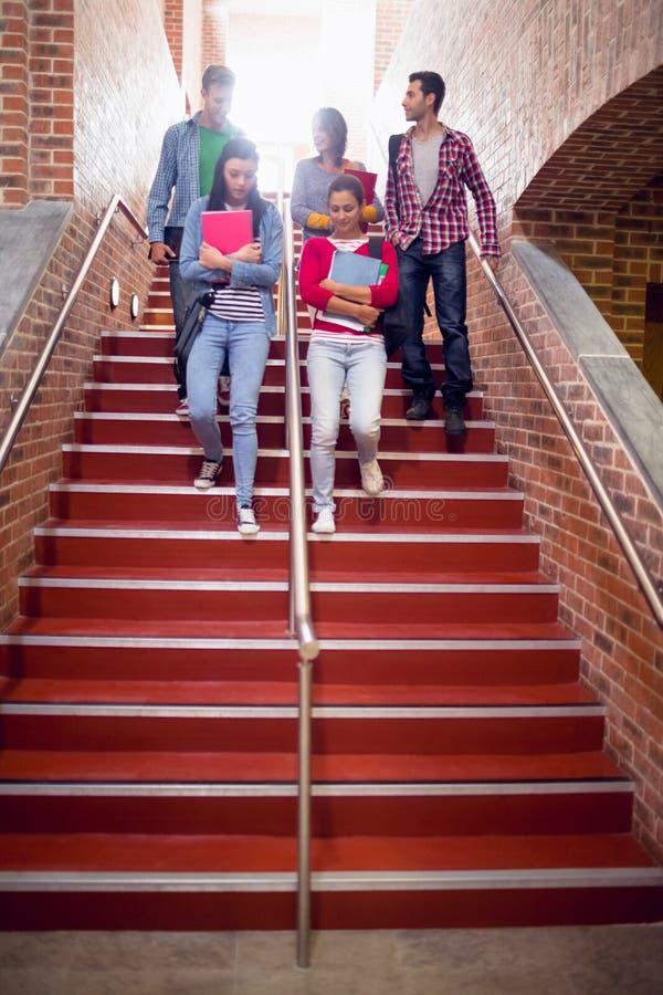 Studenci collegu chodzi w dół schodki w szkole wyższa obrazy stock