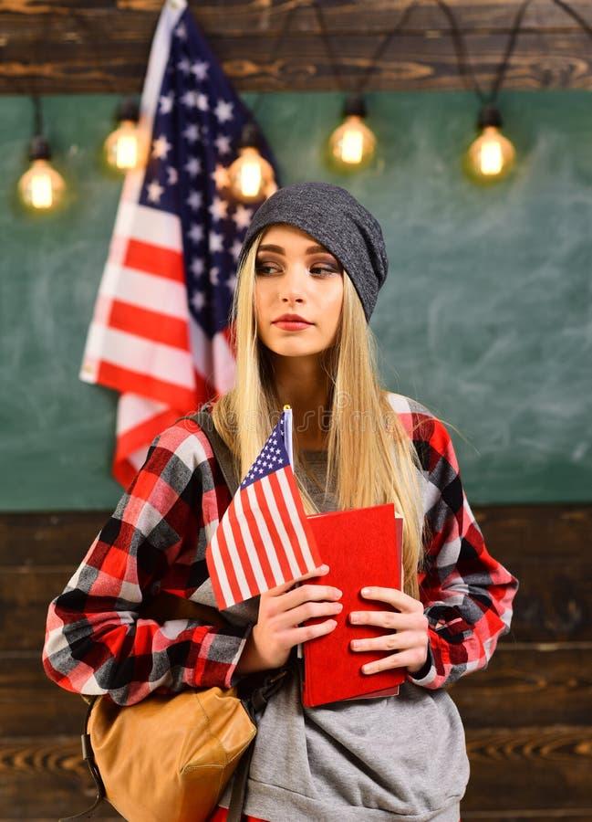 Studenci collegu w bibliotece przeciw złożonemu wizerunkowi usa flaga państowowa Angielski żeński uczeń z flagą amerykańską fotografia royalty free