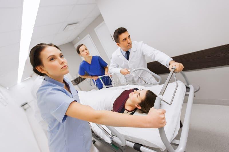 Studenci medycyny z kobietą na szpitalnym nosze na kółkach przy nagłym wypadkiem obrazy stock