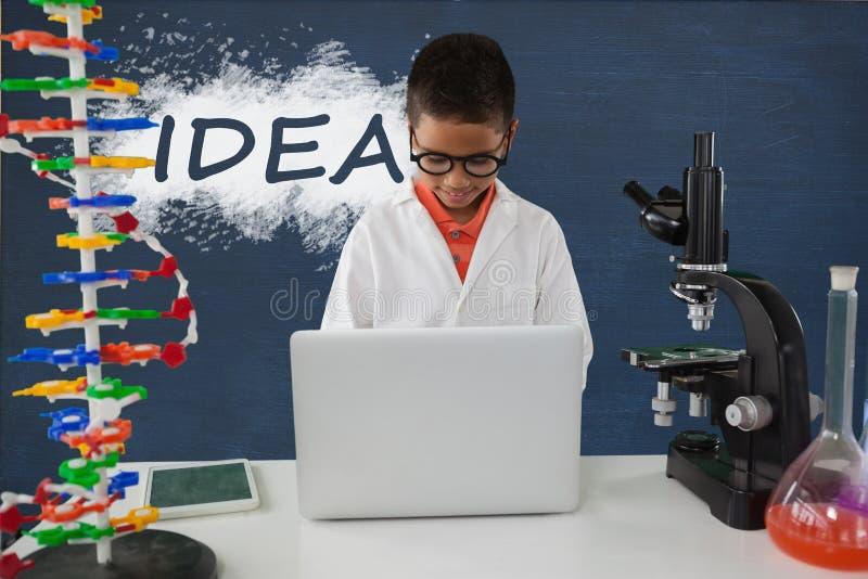 Studencka chłopiec przy stołem używać komputer przeciw błękitnemu blackboard z pomysłu tekstem zdjęcia royalty free