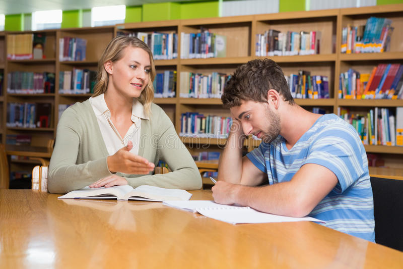 Studencka dostaje pomoc od adiunkta w bibliotece obrazy stock