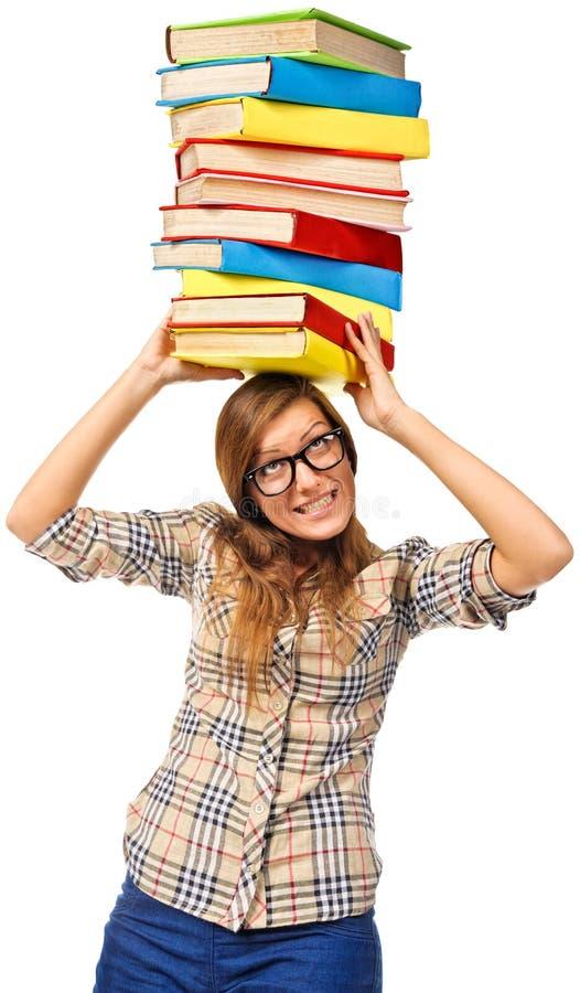 Studencka dziewczyna ono zmaga się z stertą książki zdjęcia stock
