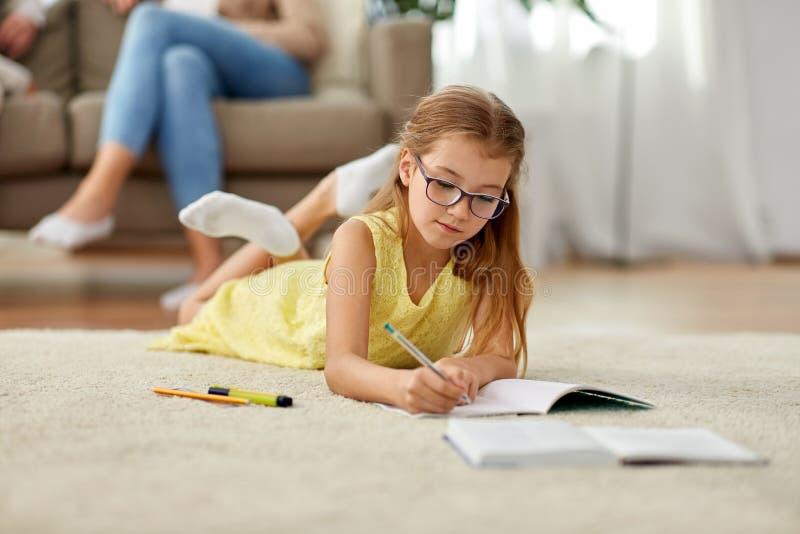 Studencka dziewczyna pisze notatnik w domu obraz stock