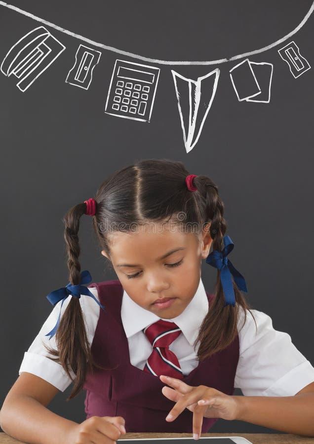 Studencka dziewczyna przy stołowym czytaniem przeciw popielatemu blackboard z szkołą i edukaci grafiką obrazy stock
