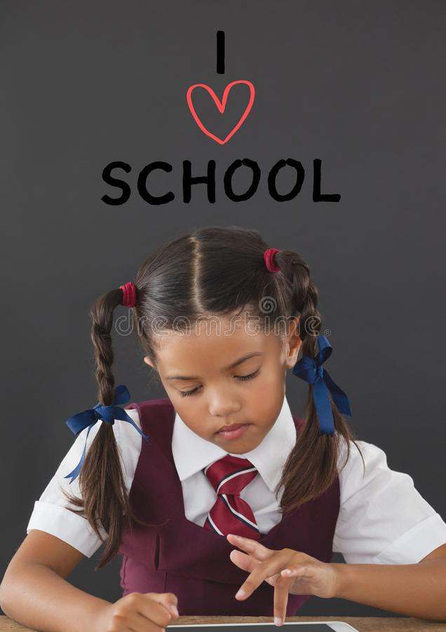 Studencka dziewczyna przy stołowym główkowaniem przeciw popielatemu tłu z kocham szkolnego tekst fotografia stock