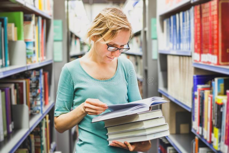 Studencka dziewczyna w bibliotecznych czytelniczych książkach, edukacja obrazy stock