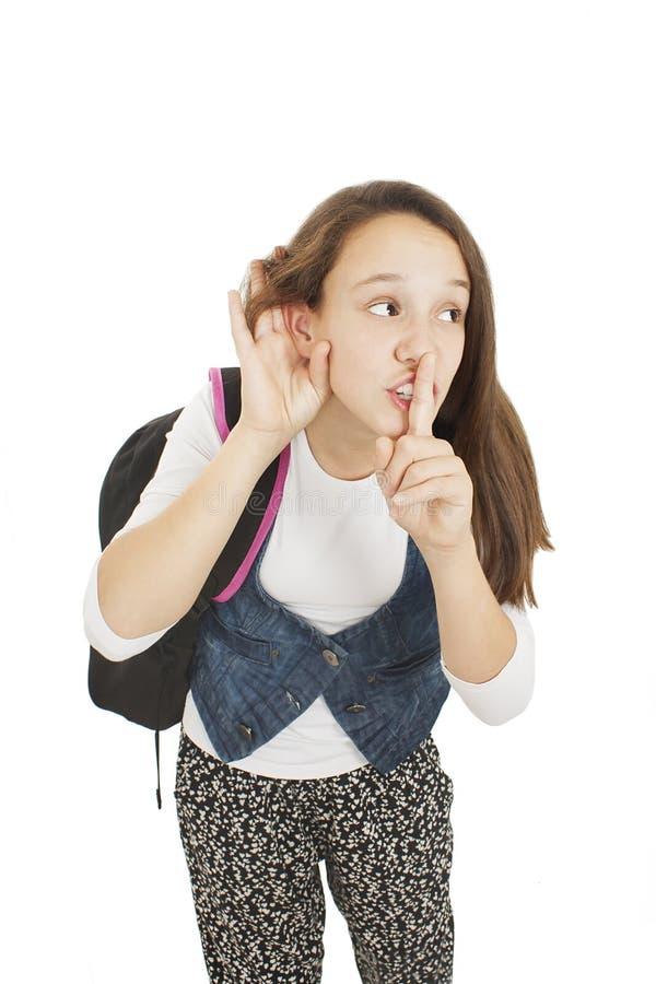 Studencka dziewczyna z palcem na usta, podsłuchuje zdjęcia royalty free