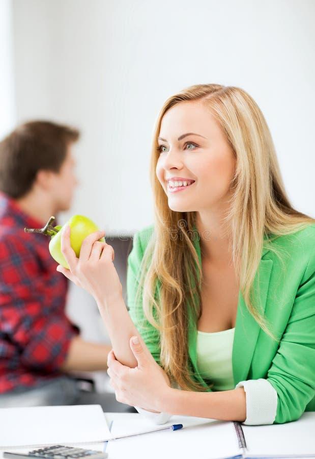 Studencka dziewczyna z zielonym jabłkiem w szkole wyższa fotografia stock